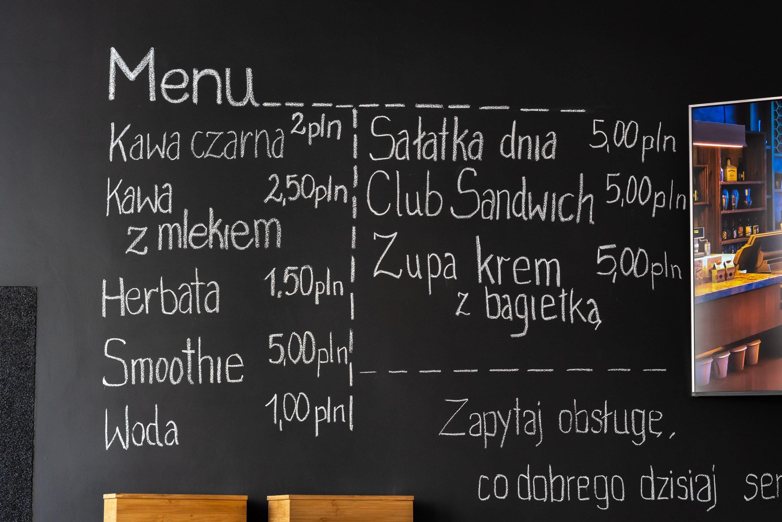 czarna ściana z menu bistro, kawa czarna 2 zł, kawa z mlekiem 2,5 zł, herbara 1,5zł, smoothie 5 zł, woda 1zł, sałatka dnia 5zł, club sandwich 5 zł, zupa krem z bagietką 5 zł, napisa: zapytaj obsługę co dobrego dzisiaj serwujemy