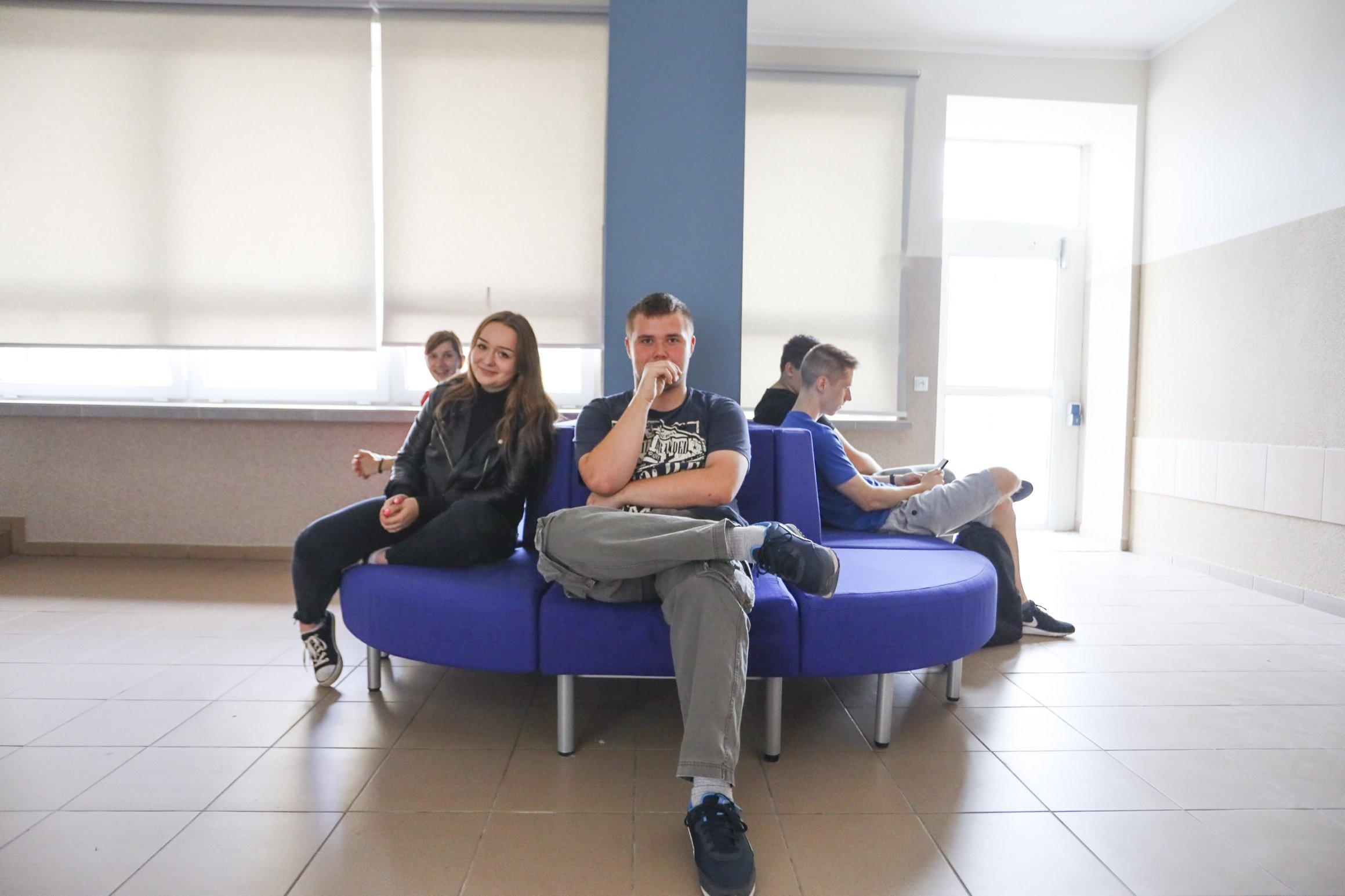 5 młodych osób siedzi na niebieskich sofach w szkole