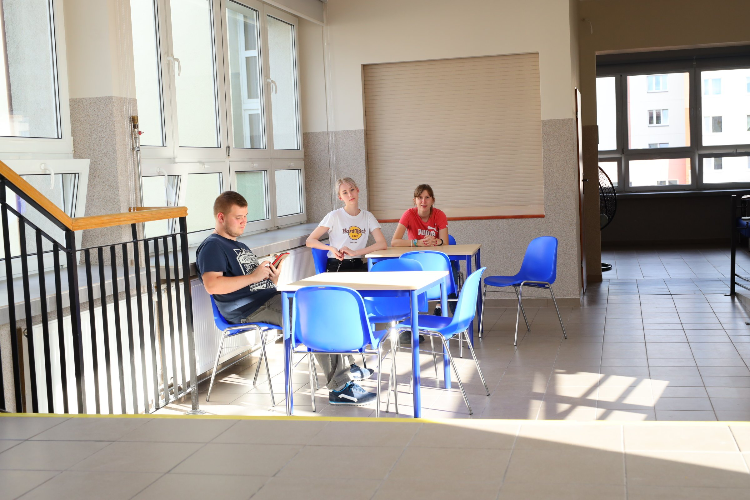 trzy młode osoby siedzą przy stolikach