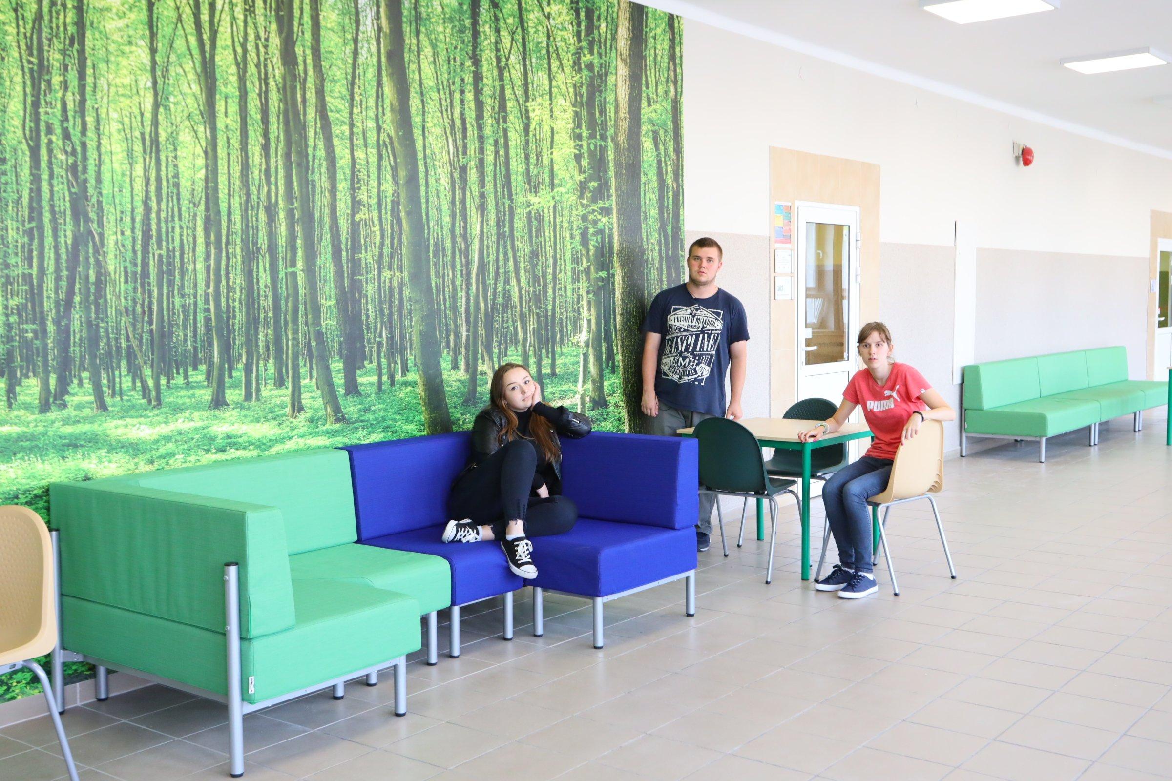 trzy młode osoby siedzą na korytarzu szkolnym na sofach i krzesłach, na ścianie fototapeta przedstawiająca las