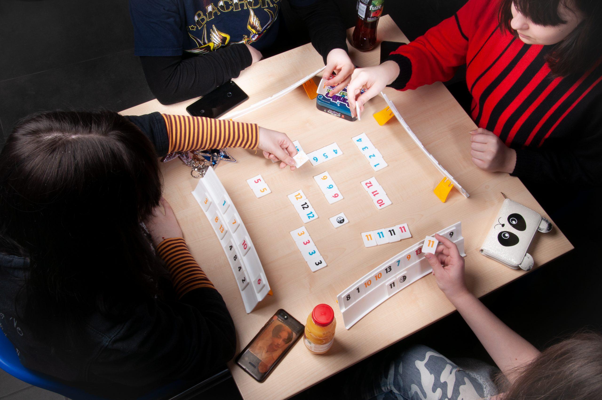 cztery młode osoby grają w grę planszową, na stoliku rozłożone elementy gry