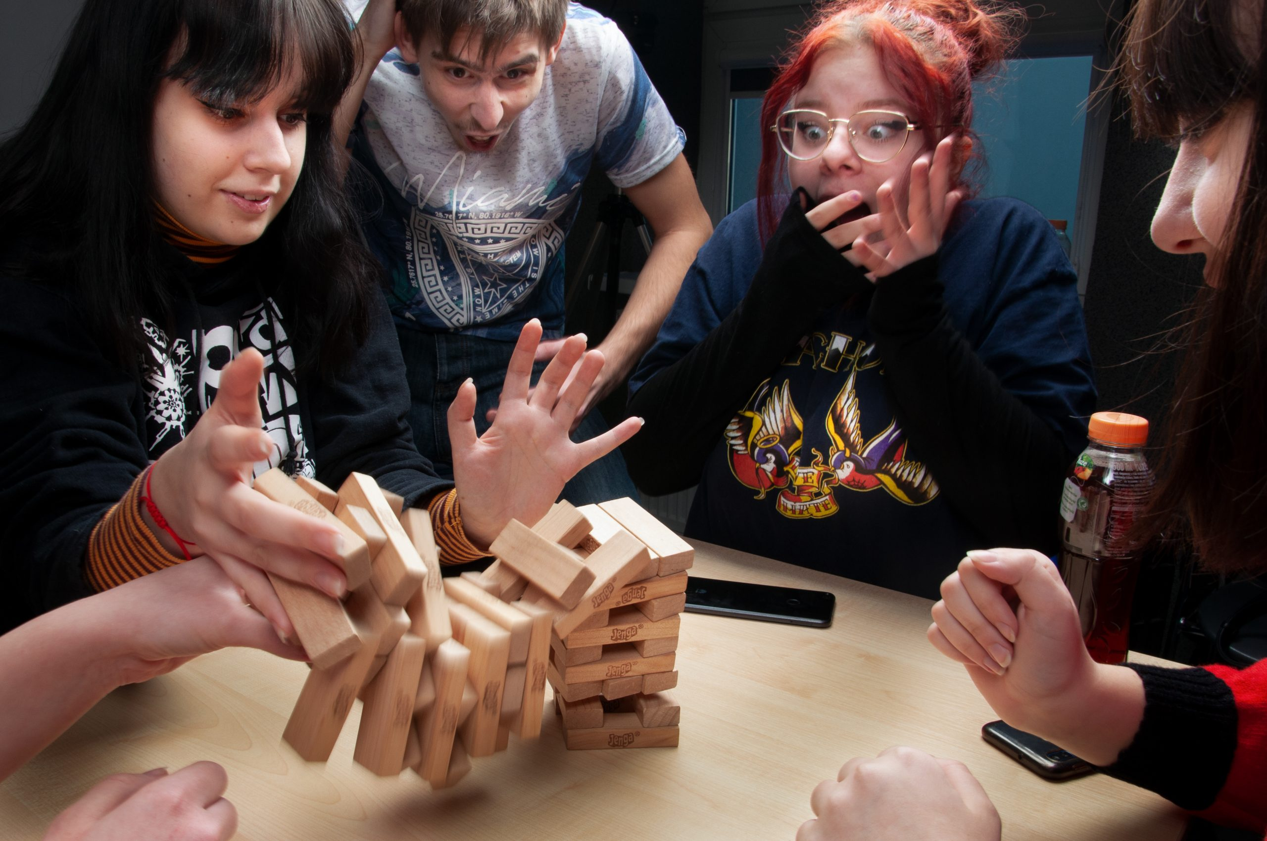 cztery młode osoby grają w grę Jenga, klosku rozsypują się na blat stolika