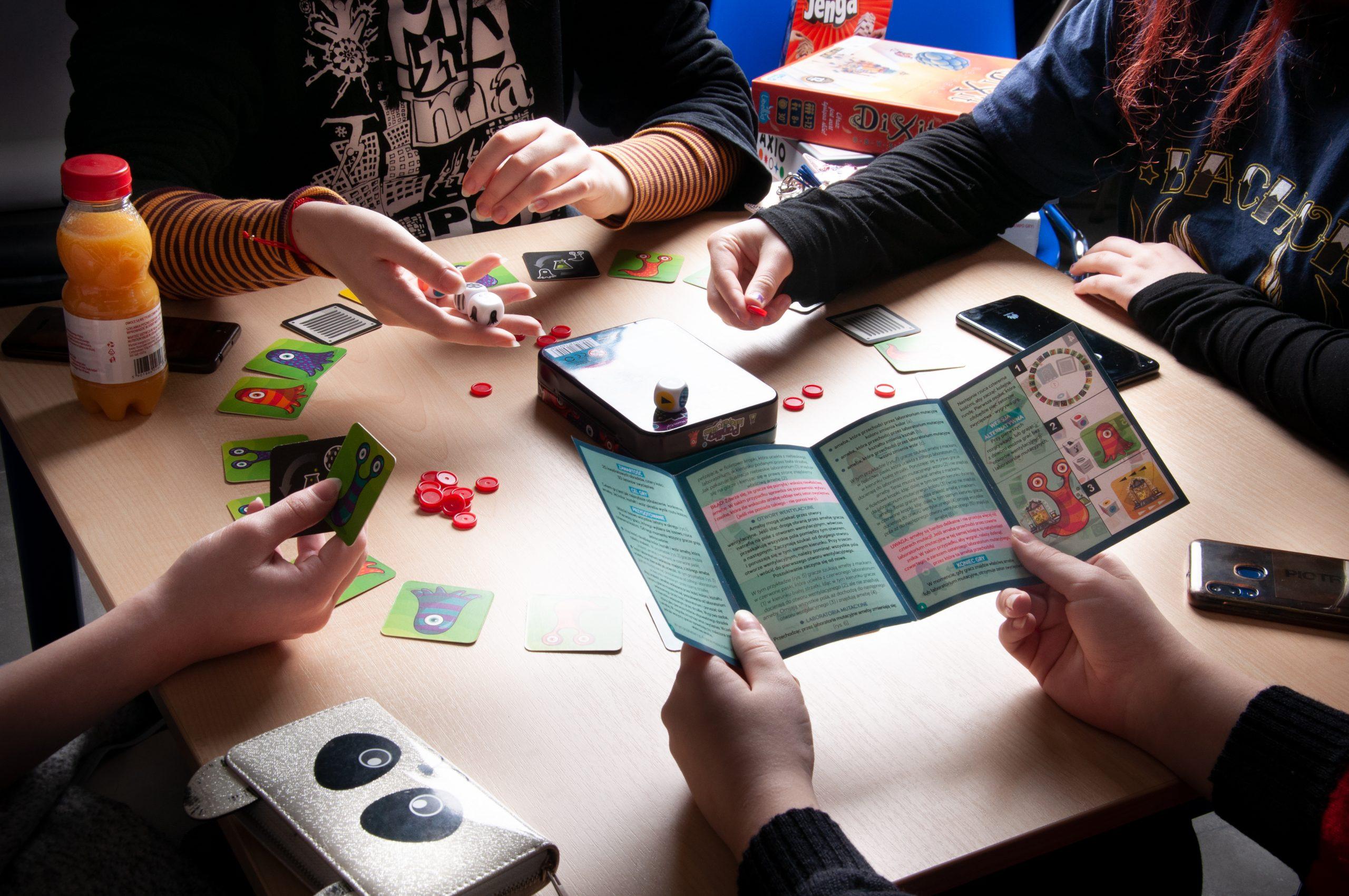 cztery osoby grają w grę planszową, na stoliku karty do gry