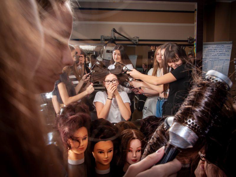 w salonie fryzjerskim grupa młodych osób układa fryzurę dziewczynie, widac głowy do ćwiczeń fryzjerskich