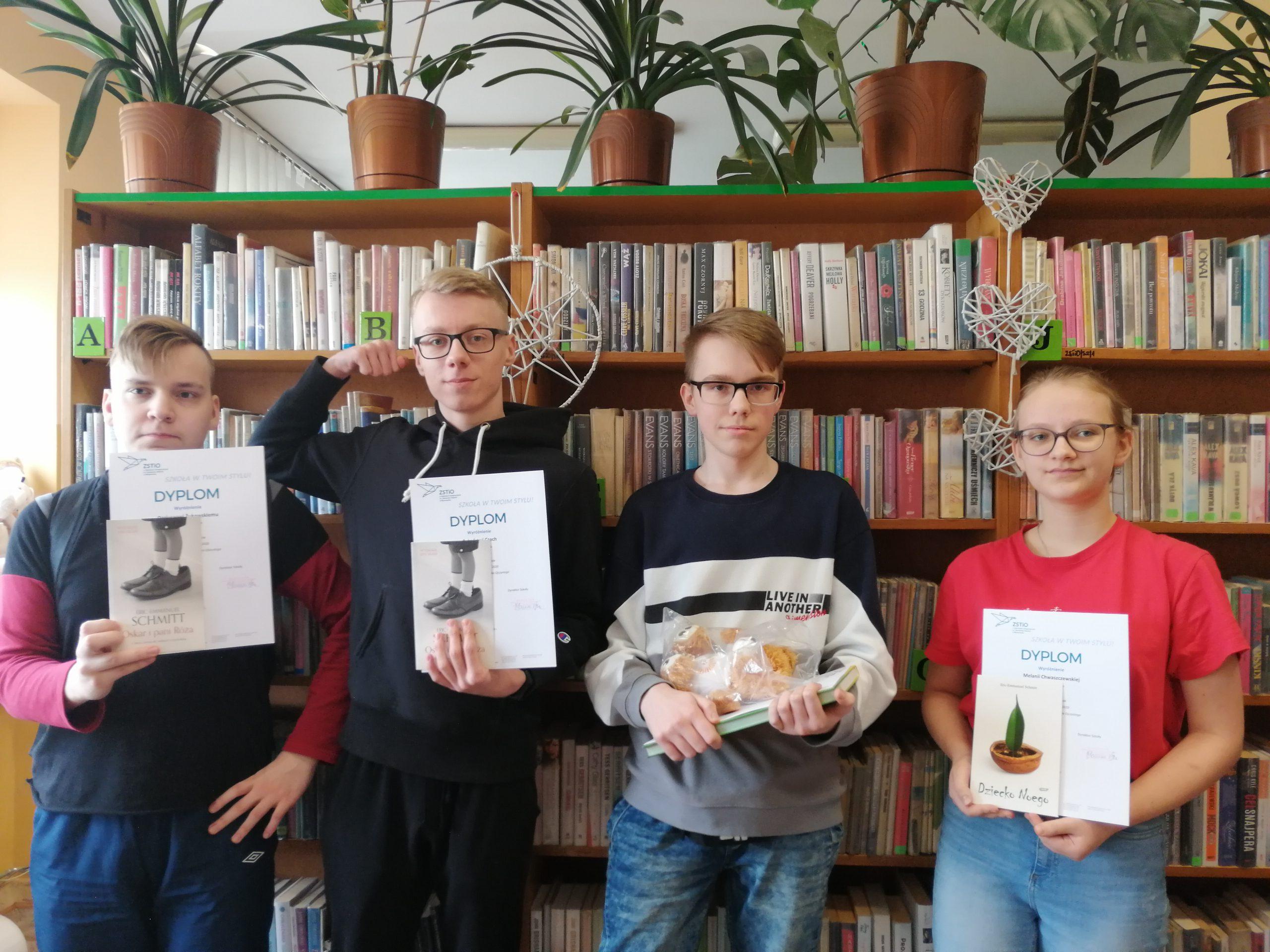 czterech nagrodzonych uczniów z dyplomami i nagrodami