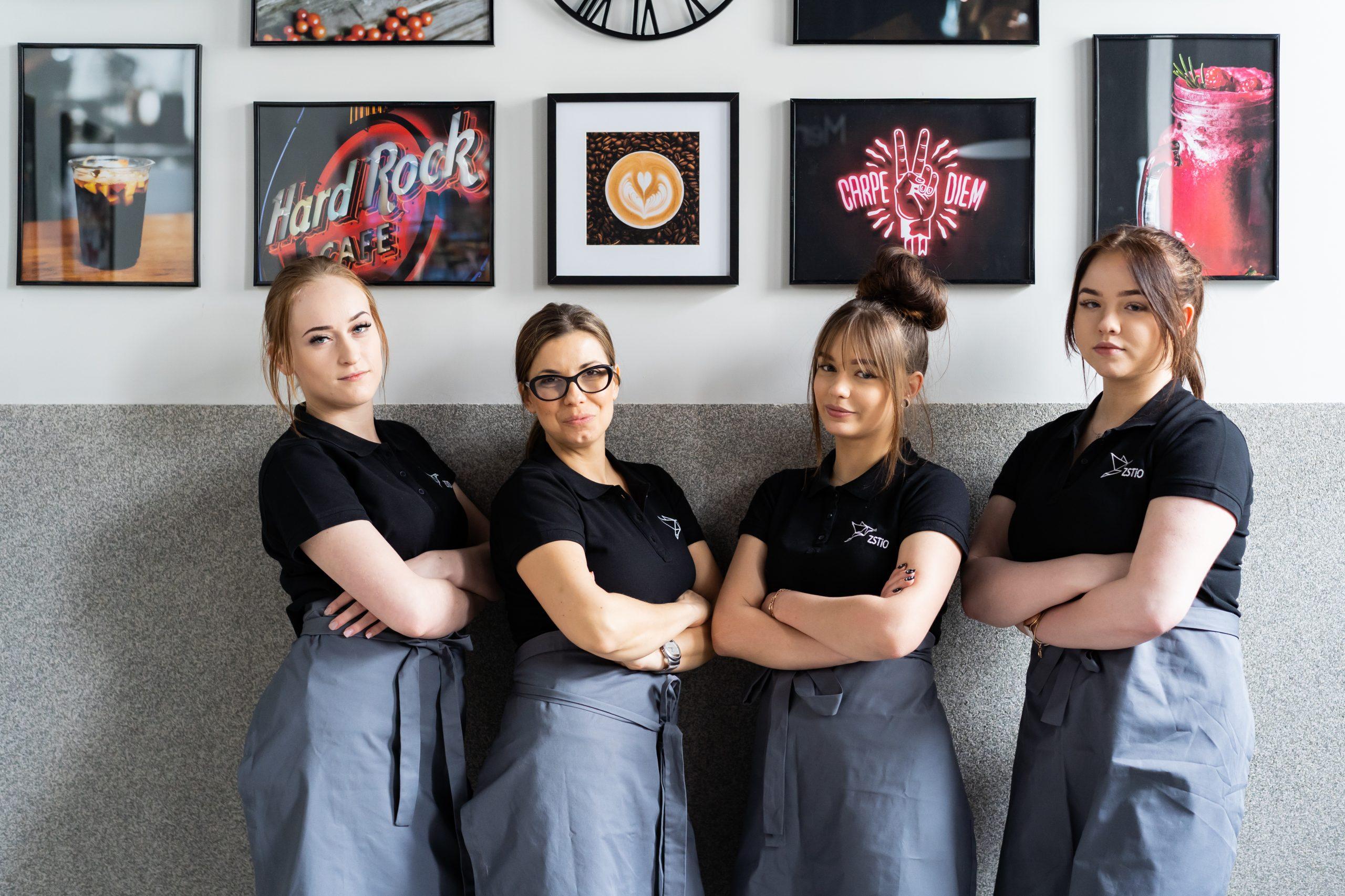 cztery kobiety ubrane w czarne koszulki z logo szkoły, na drugim planie obrazki na ścianie