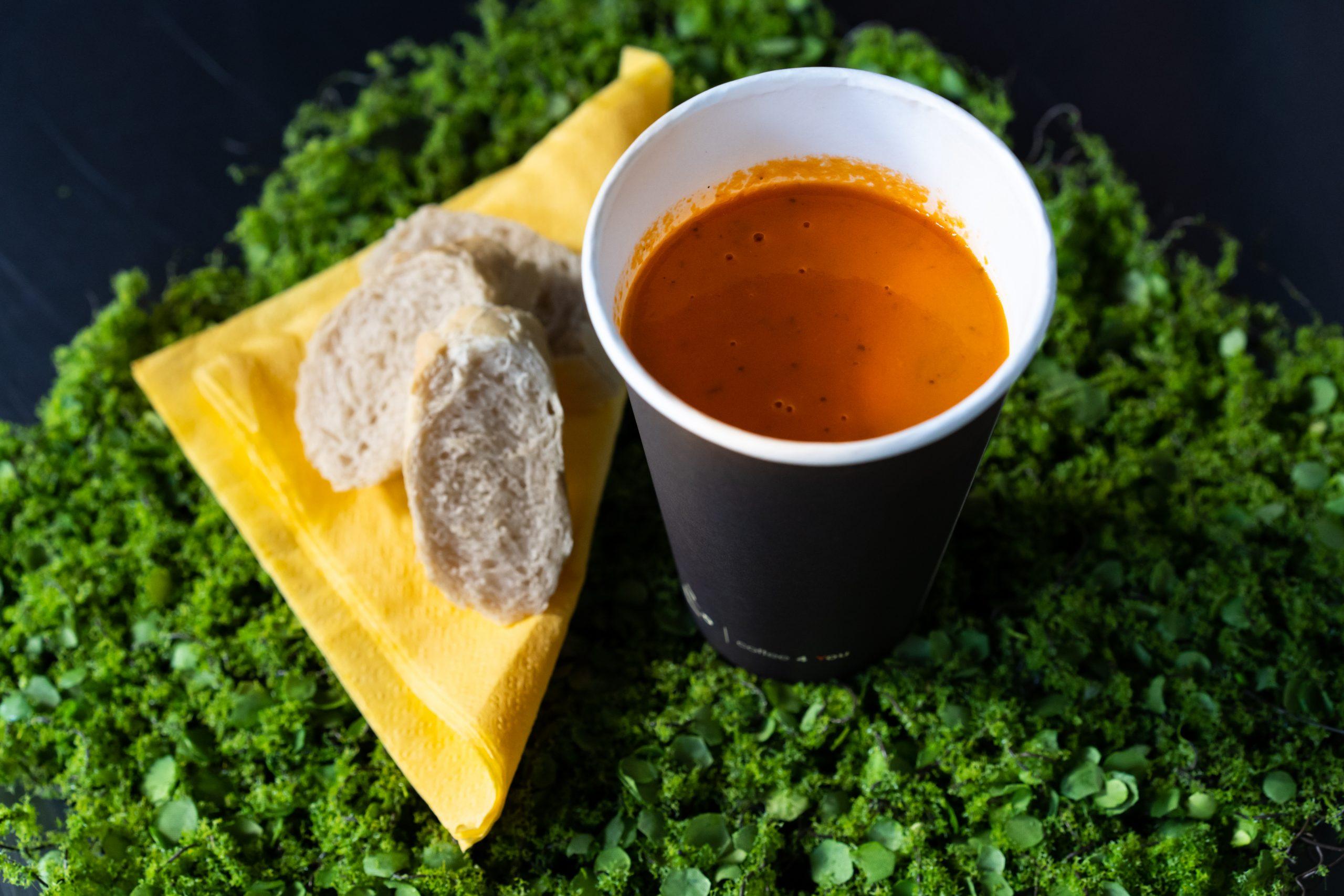 na zdjeciu zupa krem w papierowym kubku , żółta serwetka i dwa kawałki białej bagietki