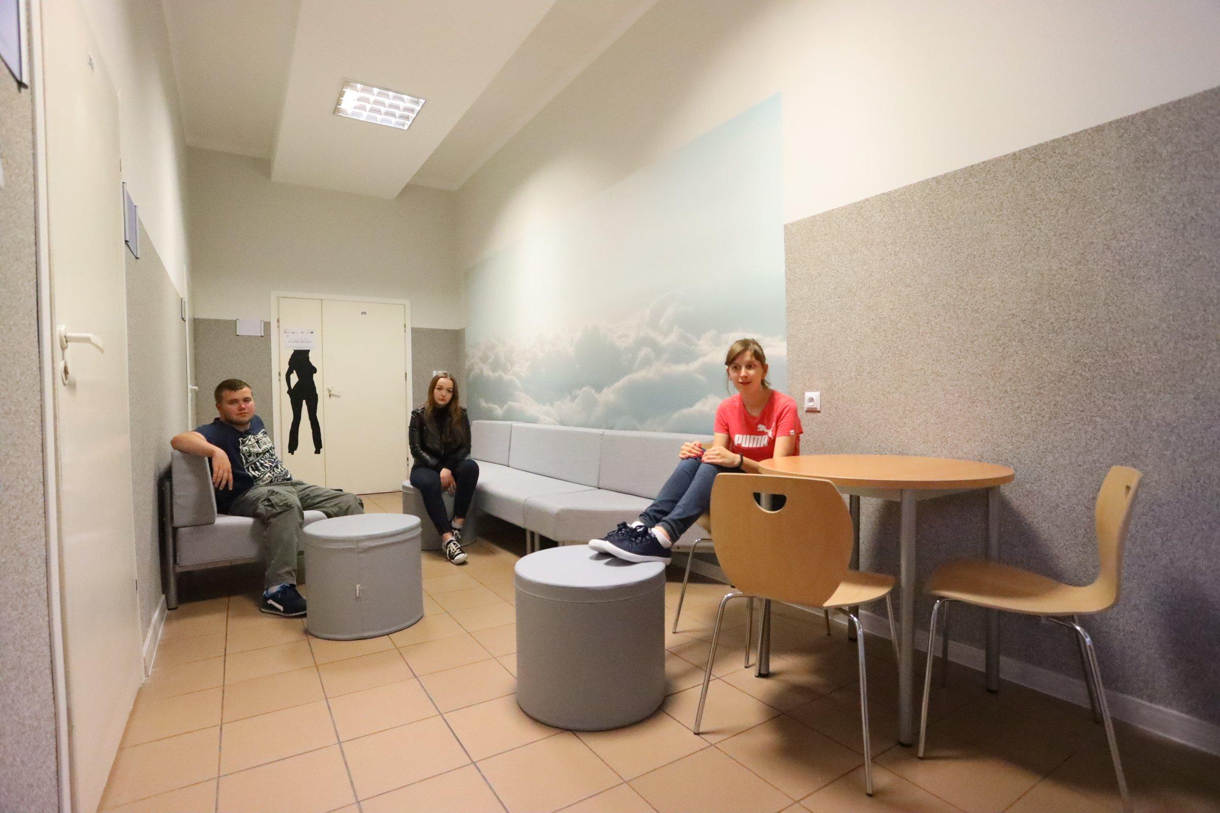 trzy młode osoby siedzą na kanapach, na ścianie tapeta z chmurami
