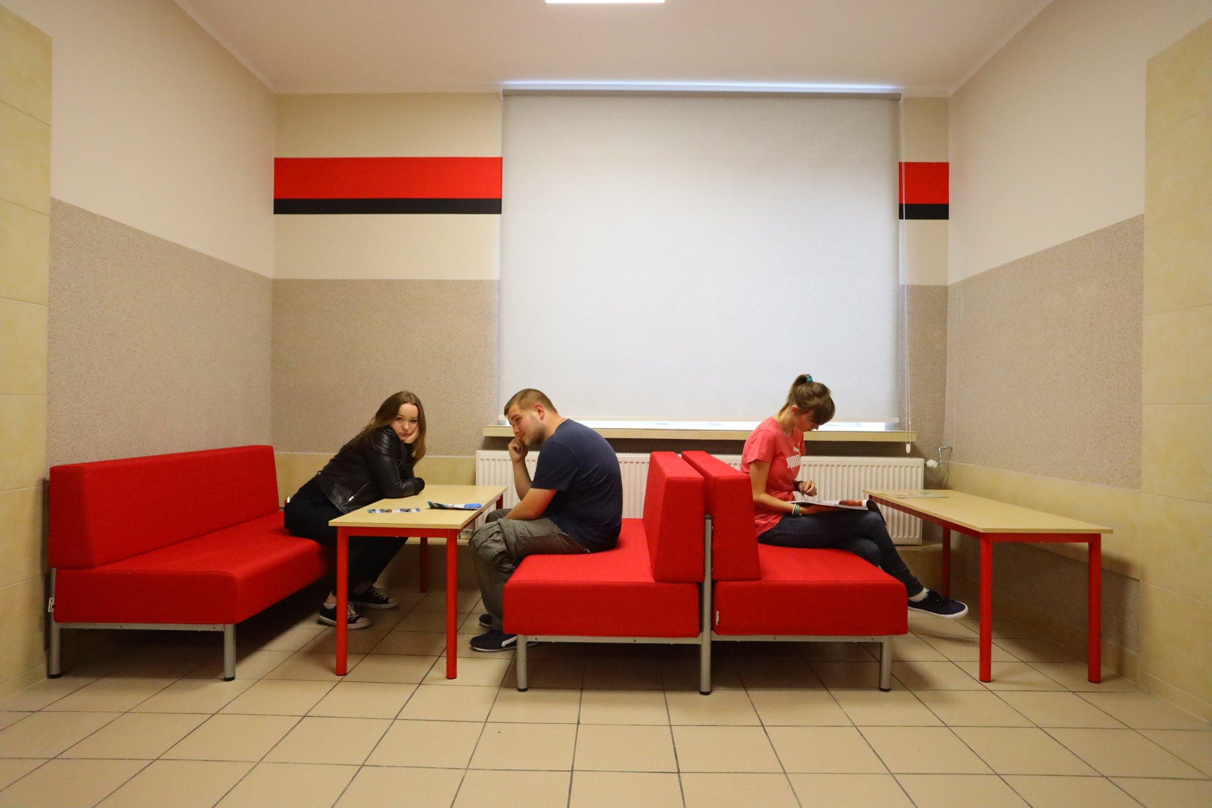 trzy młode osoby siedzą na czerwonych sofach