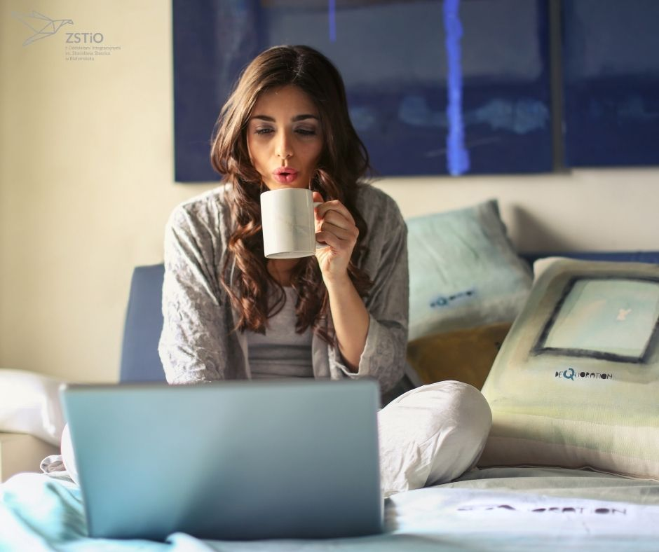 młoda dziewczyna siedzi na łóżku z laptopem, pije kawę, w tle poduszki.