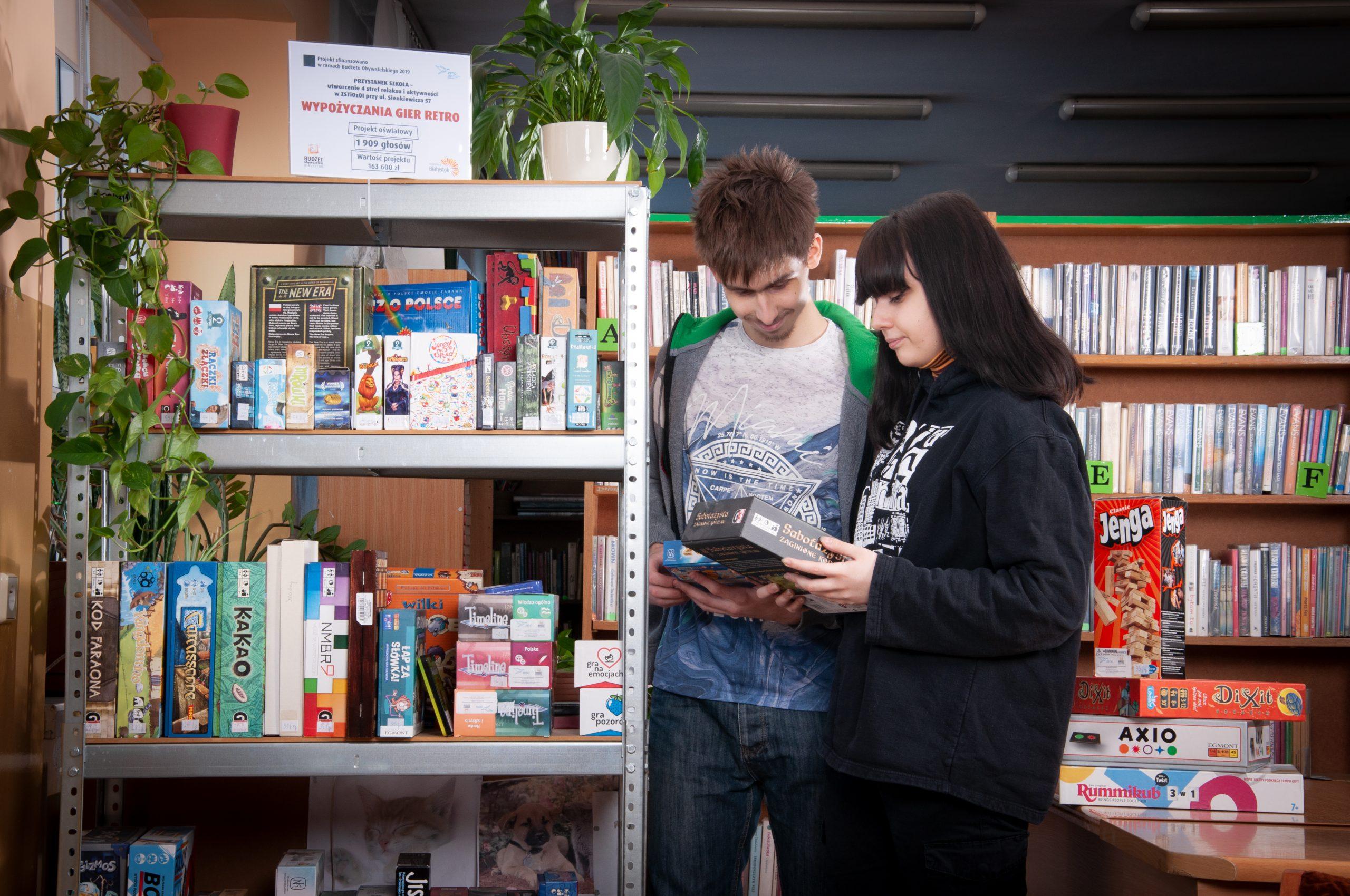 dwie młode osoby stoją przy regale, na którym są gry planszowe