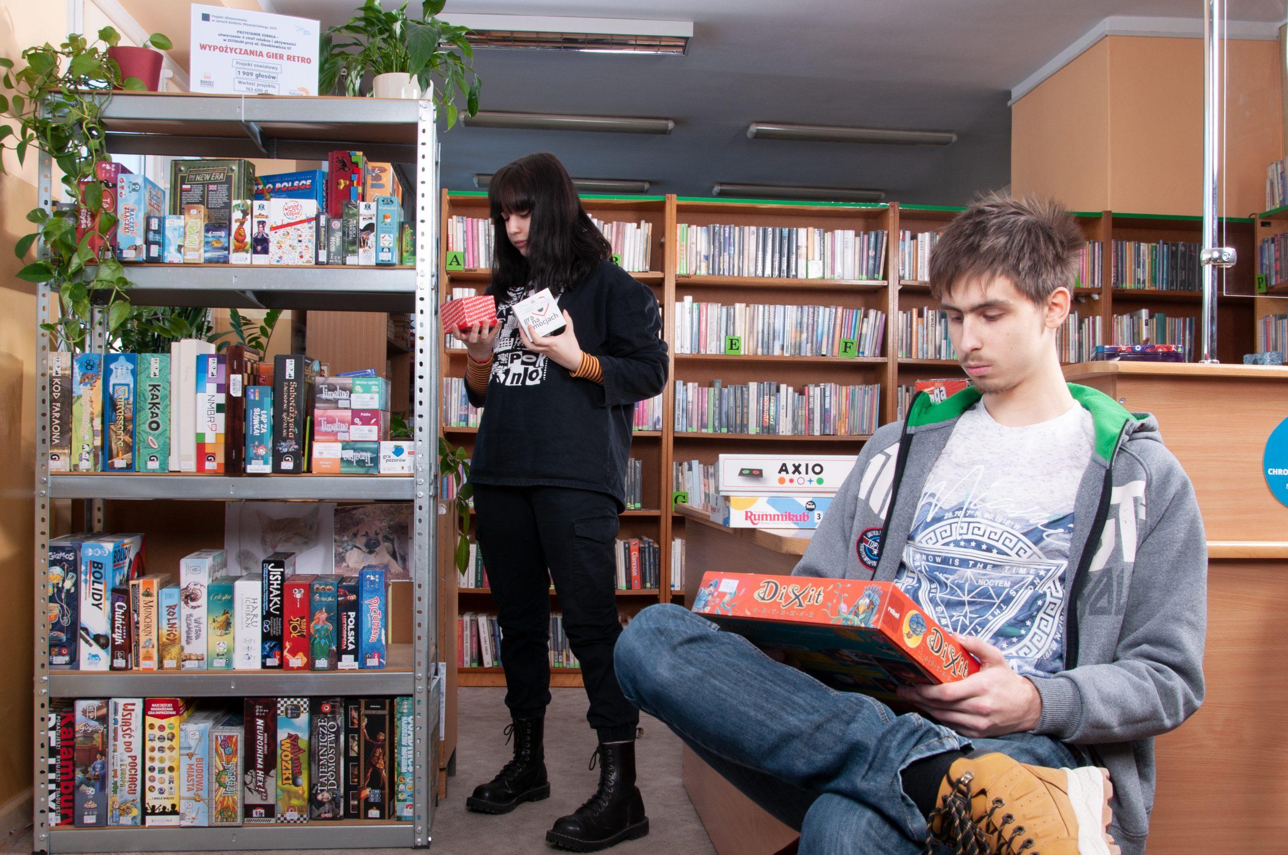 młody chłopak ogląda grę planszową, młoda dziewczyna wybiera grę planszową