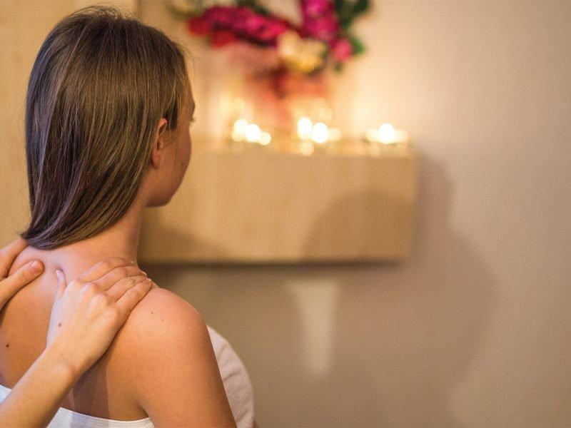 kobieta siedi tyłem, na jej ramionach znajdują się dłonie masazysty, w tle kwiaty i świece