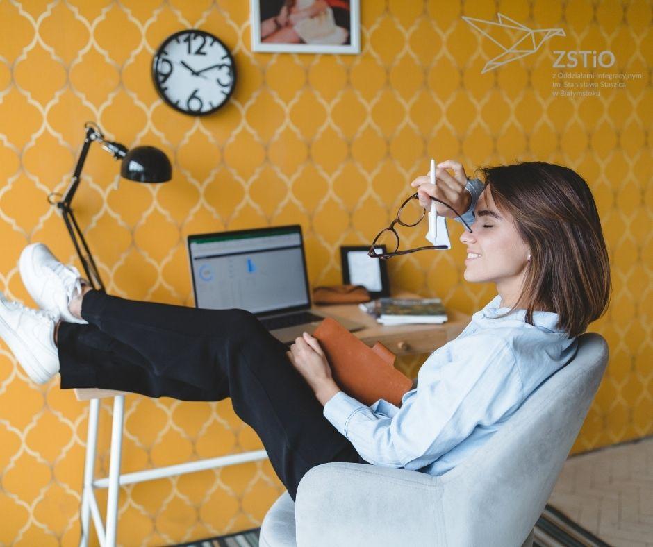 młoda dziewczyna siedzi przy biurku, w ręku trzymanotes i okulary, w tle laptop, lampka i żółta tapeta