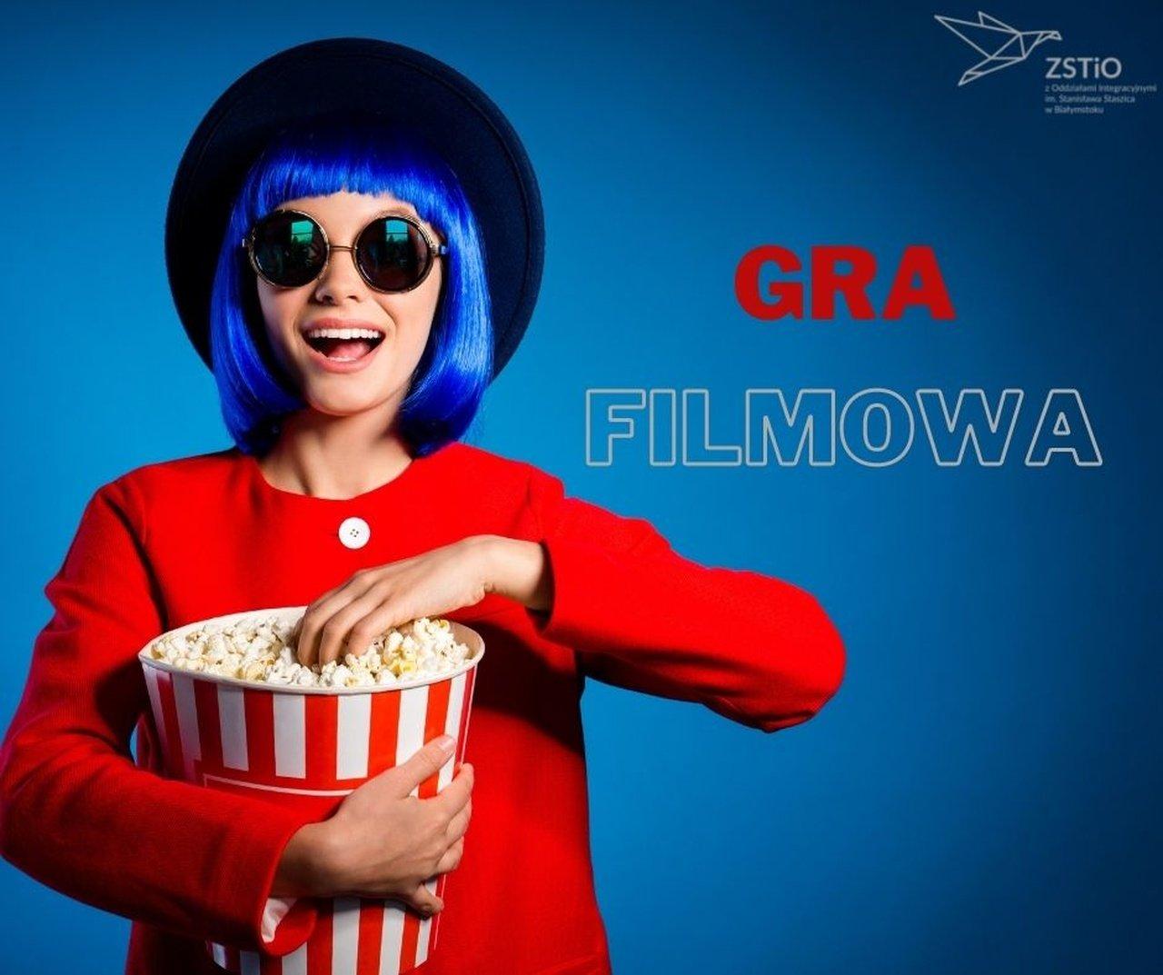 niebieskie tło, na pierwszym planie dziewczyna w kapeluszu z niebieskimi włosami, w czerwonej koszuli trzyma popcorn
