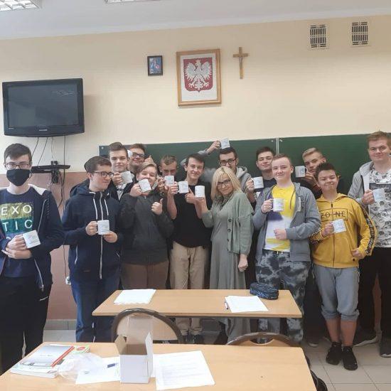 grupa ucznió w klasie, po srodku kobieta, uczniowie trzymają kubki