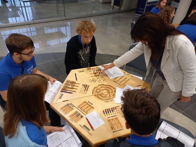 4 młodych ludzi siedzących przy drewnianym stole, trener tłumaczący zasady gry