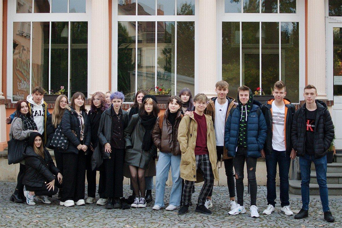 grupa młodych ludzi stoi na tle przeszklonego budynku