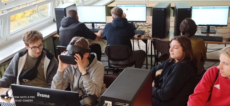grupa młodych ludzi, sala informatyczna, komputery