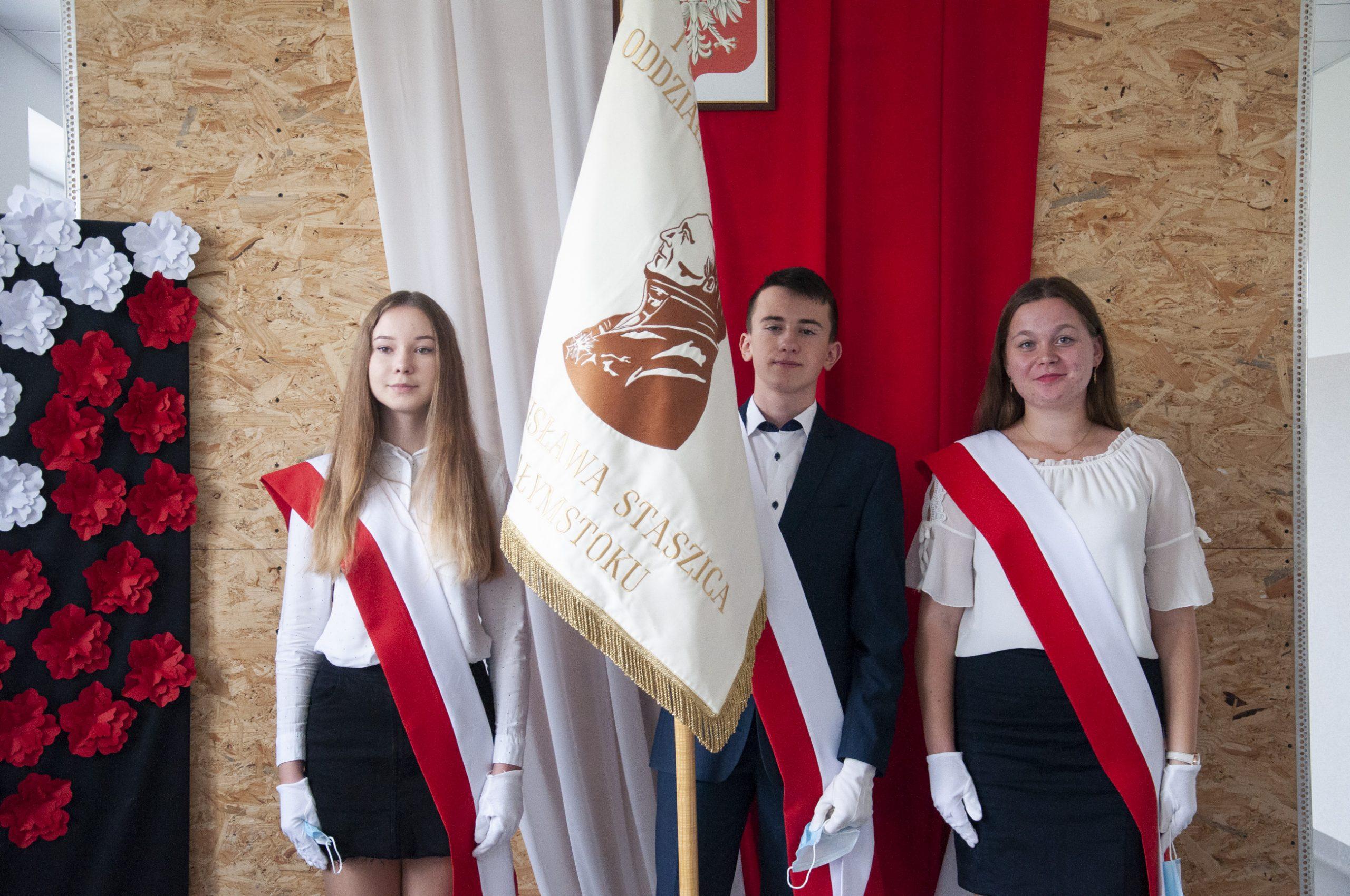 w tle flaga polska, trzy młode osoby w galowym stroju, chłopak trzyma sztandar szkoły