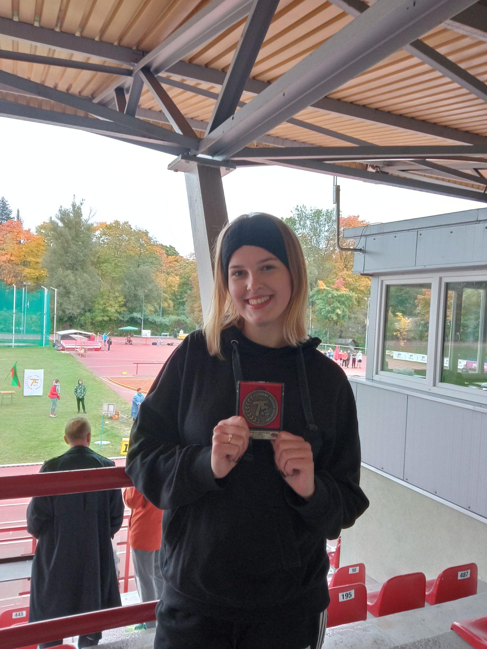 młoda dziewczyna , w ręce trzyma srebrny medal