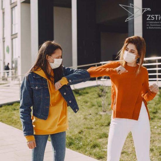 dwie młode kobiety w maseczkach, witają się łokciami